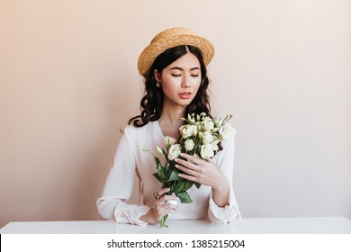 Appealing asian girl holding white flowers. Studio shot of blissful chinese model with eustoma bouquet.