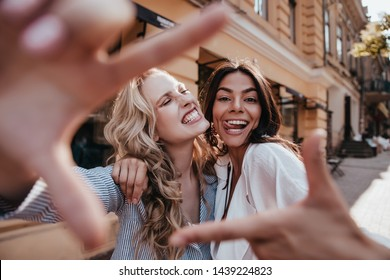 Appealing fair-haired woman fooling around with friend. Latin brunette girl spending time outdoor with sister.