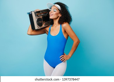 Appealing girl in old school sportswear standing on blue background. African female model with boombox posing after aerobics.