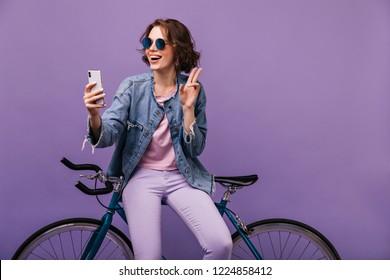 Appealing girl in purple pants making selfie in studio. Good-humoured young lady in denim jacket sitting on her bicycle.