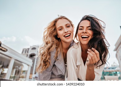 Appealing long-haired girls posing on sky background. Laughing ladies enjoying weekend together.