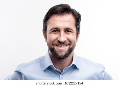 Appealing smile. The portrait of a handsome dark-haired middle-aged man in a blue shirt smiling at the camera while posing against a white background