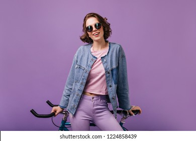 Appealing woman in denim jacket posing with bicycle. Indoor shot of confident curly lady isolated on purple background.