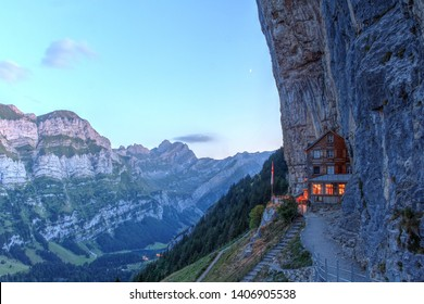 APPENZELL, SWITZERLAND - August 16 2018: Sunset view of the magical Aescher Cliff and the moutain restaurant catering to hikers. A crescent moon is visible above the cabin.