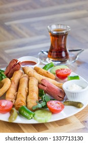 Appetiser plate with Turkish pastry (borek), onion rings, sausages and  sauces