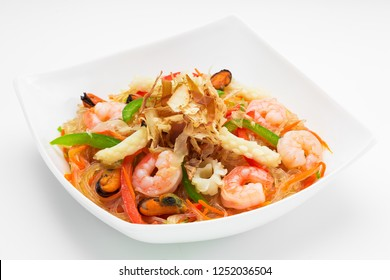 Appetising cellophane noodles with seafood in a white plate, close up on a white background