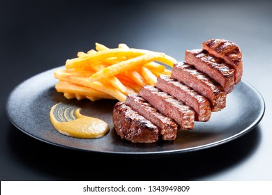 Appetising steak slices levitate above the black plate. Creative shot of steak and french fries on a dark background