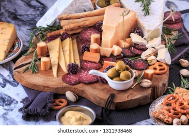 Appetizer Board. Cheese plate with cheeses, crackers, veggies, nuts, variety of meat and toppings. Charcuterie board.