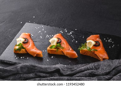 Appetizer bruschetta with fillet salmon, olives and lemon on ciabatta bread on stone slate background.
