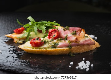appetizer bruschetta with tomato and bacon, cheese on black slate board