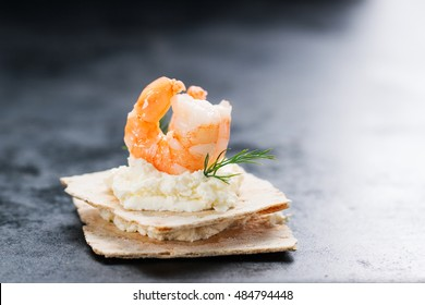 Appetizer canape with shrimp, cheese and dill on a small loaf of bread, closeup