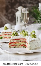 appetizer for Christmas or New Year. snack cake of pancakes with trout, avocado, cucumber, cheese. Decorated with Romanesco broccoli in the form of Christmas trees and cottage cheese as snow.