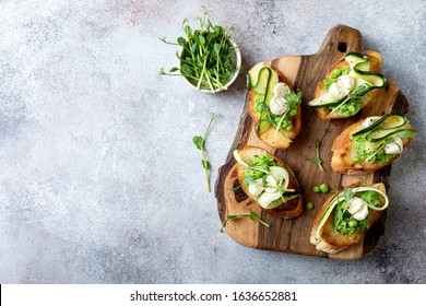 Appetizer crostini with mashed green pea, mozzarella, pea sprouts and zucchini ribbons on wooden board. Delicious healthy snack, spring appetizers