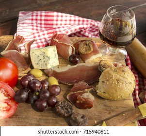 Appetizer food on wooden board. Bread,olives,grape,tomato,bruise slices,dry fig, moldy cheese and drink in crystal time glass. Close up view.
