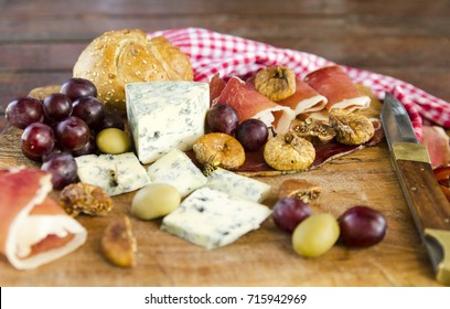 Appetizer food on wooden board. Bun Bread, olives, grape, bruise slices, dry fig, moldy cheese. Delicious Picnic.