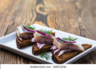 Appetizer food, open sandwich with herring and red onion