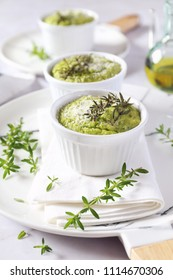 Appetizer: green vegetable soufflе with grated Parmesan cheese on light background and olive oil, three servings