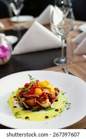 Appetizer with grilled octopus, potatoes and vegetables on restaurant table