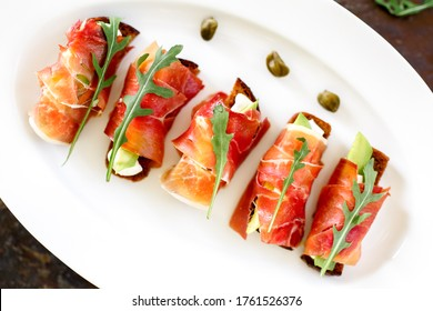 Appetizer with ham. Bread with avocado and cheese wrapped in prosciutto
