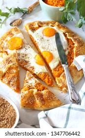Appetizer: homemade carrot pie galette with eggs, sesame dressing