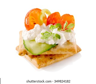 appetizer on crackers with cream cheese and vegetables close-up isolated on white background