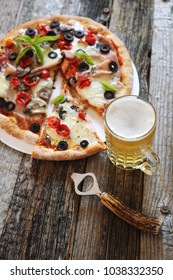 Appetizer: pizza and mug of lager beer. Focus selective