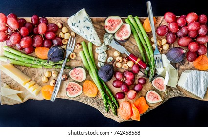 Appetizer platter with meat, cheese, and fruit on a wooden cutting board