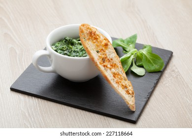 Appetizer sauteed garlic spinach dish in cup, baked bread slice  with  melted cheese served on black stone