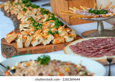 Appetizer of savory pizzas and other salami in a wedding party.