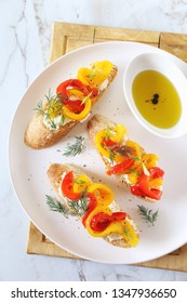 Appetizer. Slice of bread, cream cheese and multi-colored grilled bell pepper with olive oil. Top view on light background