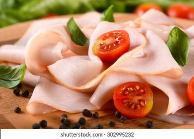 appetizer of sliced turkey breast rolled up on the cutting board