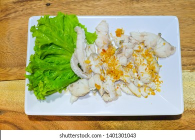 appetizer. Snapper Scalded.Sliced white fish Place on a plate.There is a green vegetable beside.With garlic sprinkled on fish meat.Thai food.at Khao Tom Shop(Street food shop).dinner