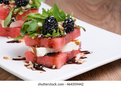 appetizer  stacked slices of watermelon, feta, arugula, blackberry sauce and nuts