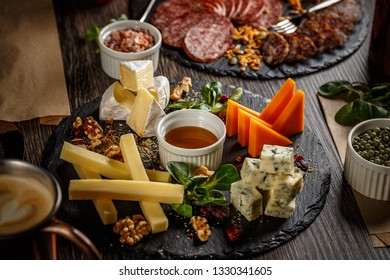 Appetizer table with antipasto snacks. Cheese and meat variety board over wooden background