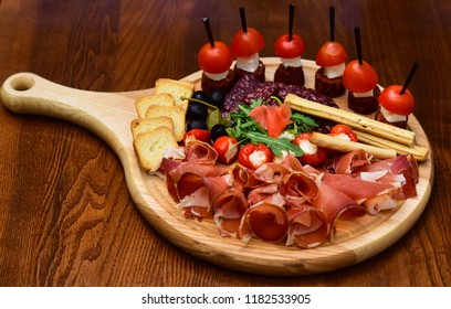 Appetizer table with italian antipasto snacks. Cold meat cuts and canape with tomatoes served on appetizer platter. The taste from space.