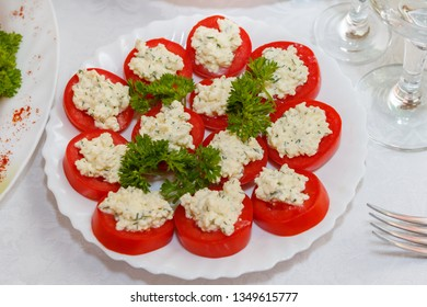 Appetizer with tomato, cheese and herbs on white dish