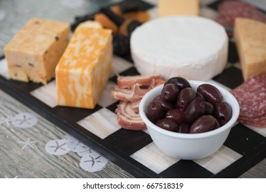 An appetizer tray with a selection of cheese, meat and olives.