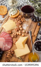 Appetizer for wine. Plateau with meat, nuts, cheese, olives, grapes, honey in a glass, crispy bread with curd cheese and glasses of wine. On a light gray background