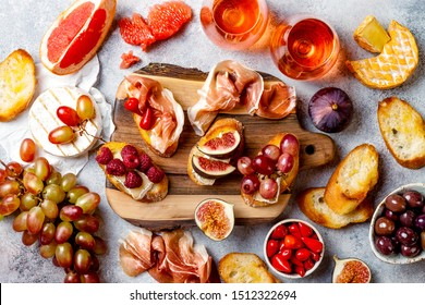 Appetizers, antipasti snacks and rose wine in glasses. Bruschetta or authentic traditional spanish tapas set, cheese and meat platter over grey concrete background. Top view