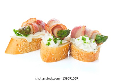 appetizers - bread slices with bacon, asparagus and soft cheese isolated om white background