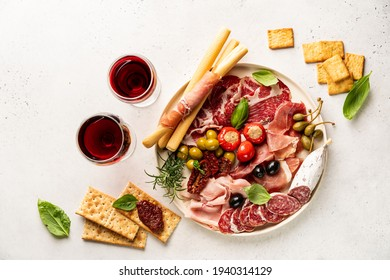Appetizers with differents antipasti, charcuterie, snacks and red wine on white background. Sausage, ham, tapas, olives and crackers for buffet party. Top view, flat lay