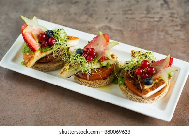 Appetizers with grilled cheese and tomatoes