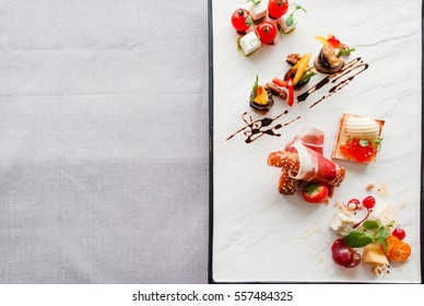 Appetizers mix flat lay, free space for text. Dish with delicatessen variety on half of picture, blank table part. Restaurant menu, recipe, event organization, creativity concept