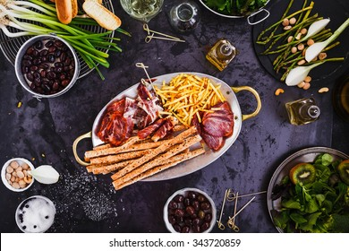 Appetizers party picnic. Mediterranean Charcuterie gourmet party overhead on rustic dark table.