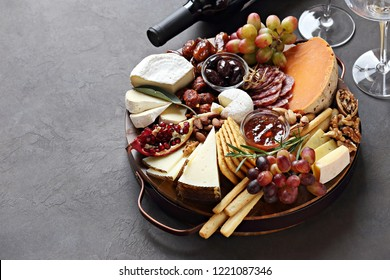Appetizers platter with various of cheese, sausage, fruits and nuts. Cheese board. Overhead view, cope space