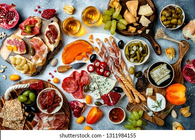 Appetizers table with antipasti snacks and wine in glasses. Bruschetta or authentic traditional spanish tapas set, cheese and meat platter over grey concrete background. Top view