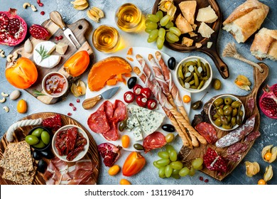 Appetizers table with antipasti snacks and wine in glasses. Authentic traditional spanish tapas set, cheese and meat platter over grey concrete background. Top view