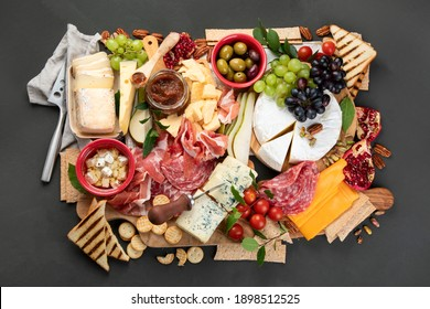 Appetizers table. Cheese, fuits and meat board on dark  background. Top view