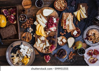 Appetizers table. Cheese variety board with tropical fruits, nuts, and wine.  Family party table. Different cheese and fruits.