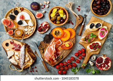 Appetizers table with italian antipasti snacks. Brushetta or authentic traditional spanish tapas set, cheese variety board over grey concrete background. Top view, flat lay